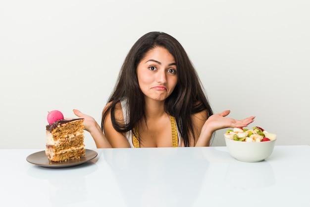 ケーキやフルーツボウルの間を選択する若いヒスパニック系女性