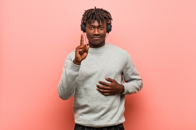 Молодой раста черный человек слушает музыку с наушниками, показывая номер один с пальцем.