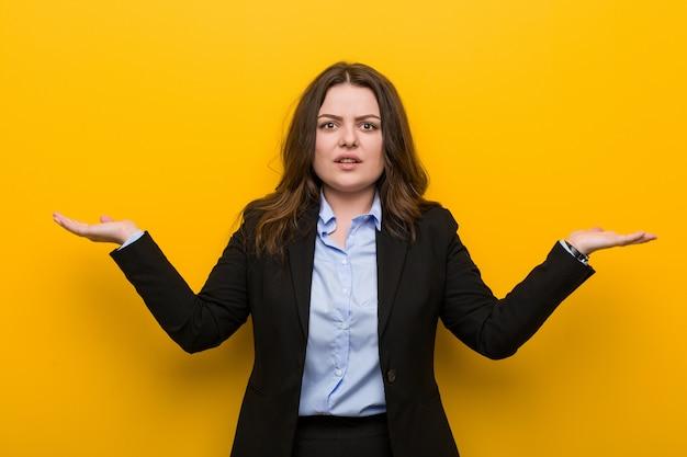 コピースペースを保持するために彼の手を上げる若いプラスサイズの白人ビジネス女性は混乱し、疑わしい。