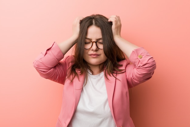 若いプラスサイズのビジネス白人女性の寺院に触れると頭痛を持っています。