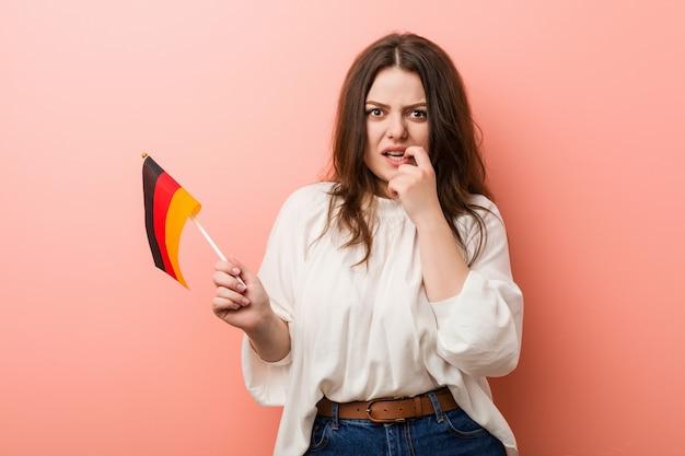 爪をかむドイツの旗を保持している若い曲線のプラスサイズの女性、神経質で非常に不安。