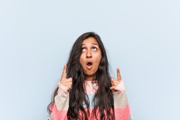 口を開けて逆さを指している若者のファッションインドの女性。