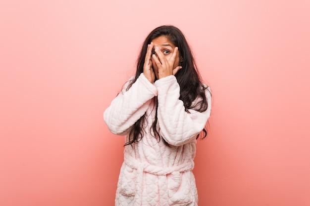 パジャマを身に着けている若いインド人女性は、恐怖と緊張の指の間で点滅します。