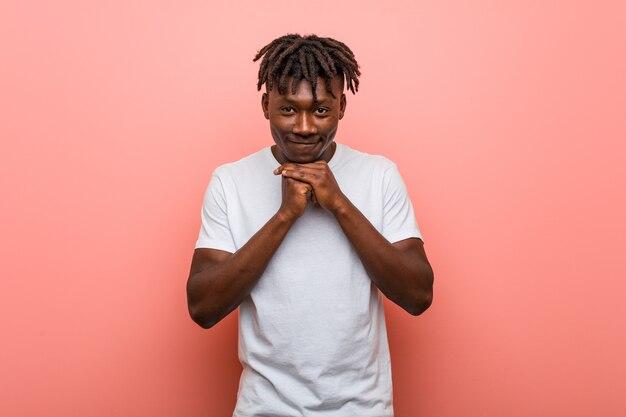 Молодой африканский черный человек держит руки под подбородком, счастливо смотрит в сторону.