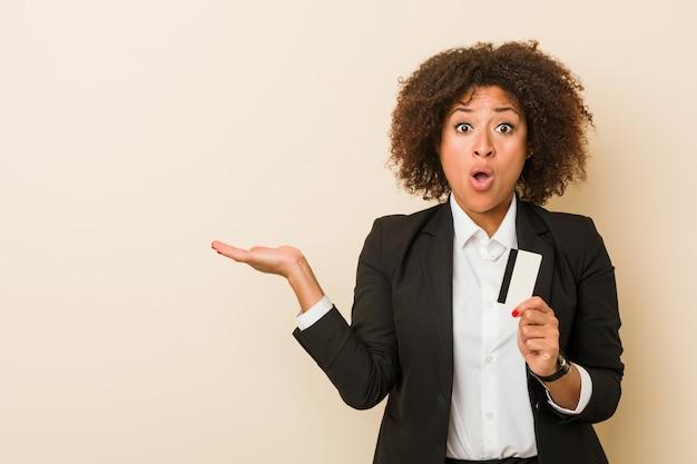 クレジットカードを保持している若いアフリカ系アメリカ人女性は、手のひらにコピースペースを保持感動しました。