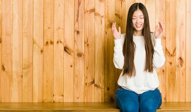 たくさん笑ってうれしそうな木製の場所に座っている若い中国人女性。幸福の概念。