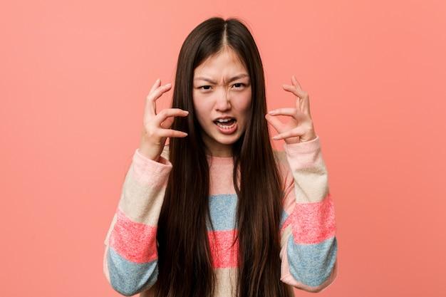 若いクールな中国人女性が緊張した手で叫んで怒っています。