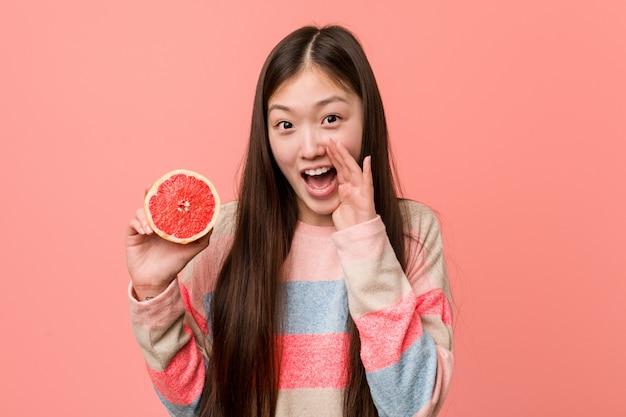 前面に興奮してグレープフルーツの叫びを持つ若いアジア女性。