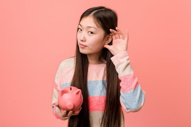 ゴシップを聴こうとして貯金を保持している若いアジア女性。