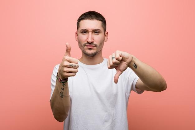 親指と親指を示すカジュアルな若者、難しいコンセプトを選択