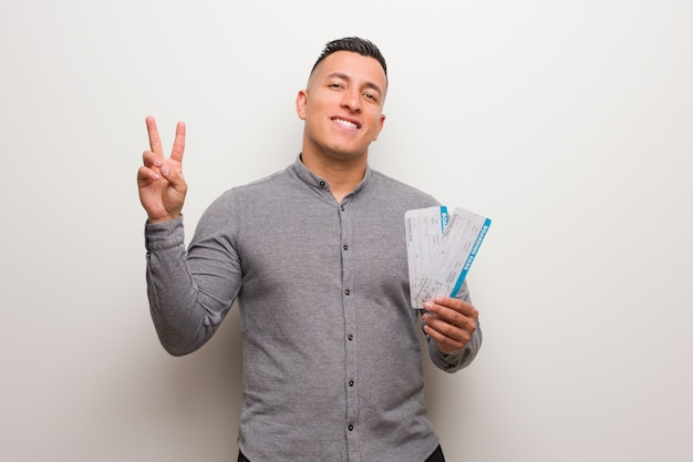 Молодой человек латинской держит билеты на самолет, показывая номер два