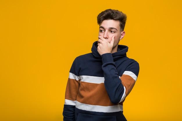 手で口を覆っているコピースペースを探している思慮深いパーカーを着ているクールな若者。