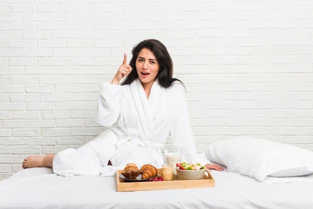 アイデアを持つベッドで朝食を取る若い曲線の女性