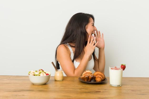 朝食を取って若い曲線の女性は大声で叫ぶ、目を開いたまま、手が緊張します。