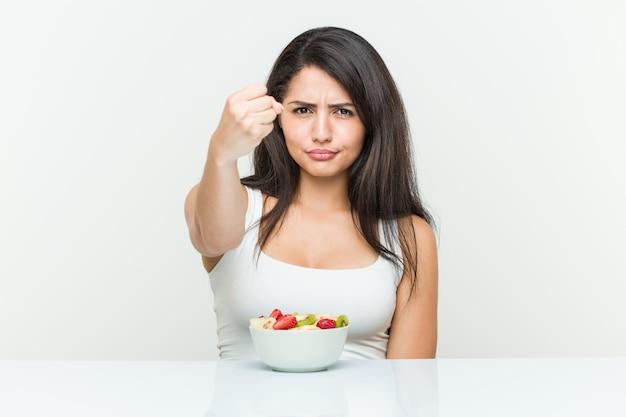 Молодая испанская женщина есть вазу с фруктами показывая кулак к камере, агрессивное выражение лица.