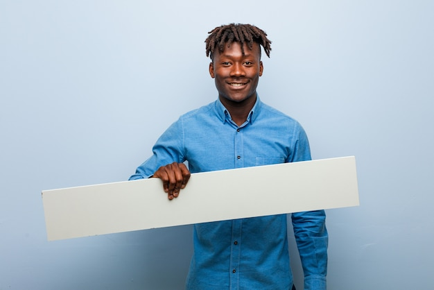 幸せ、笑顔、陽気なプラカードを保持している若いラスタ黒人男性。