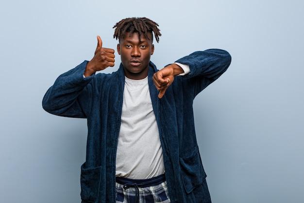 親指アップと親指ダウンを示すパジャマを着ている若いアフリカ黒人男性