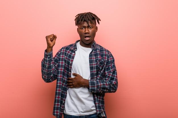 若いアフリカ黒人男性の頭の後ろに触れる、考えて、選択をします。