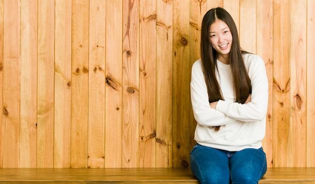 笑って、楽しんで木の場所に座っている若い中国人女性。