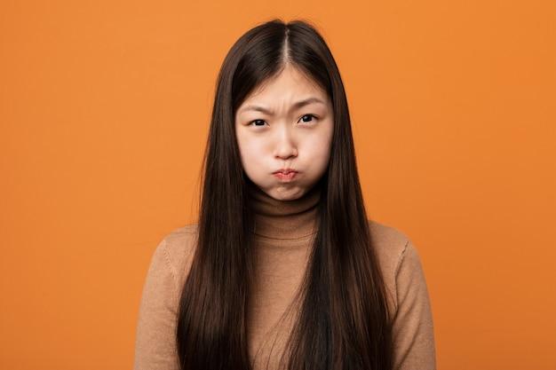 若いかなり中国の女性は頬を吹く、疲れた表情をしています。