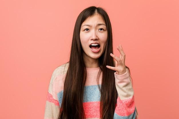 怒りで叫んでいる若いクールな中国人女性。
