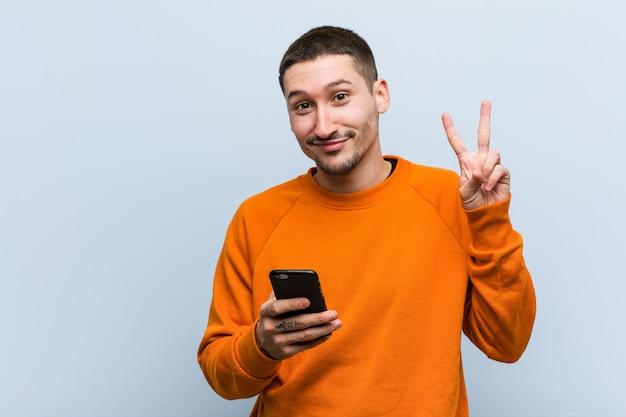 勝利のサインを示し、広く笑顔の携帯電話を保持している若い白人男。