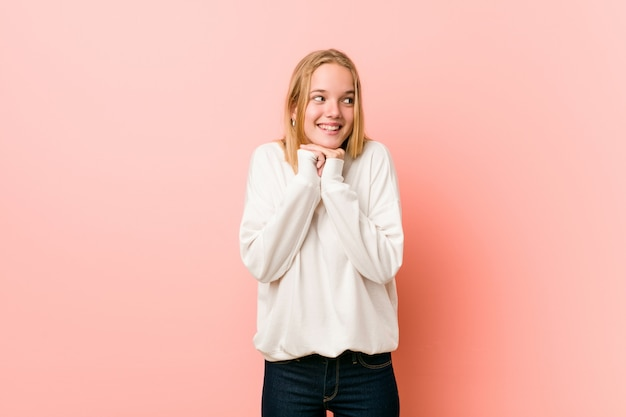 Молодая блондинка подросток женщина держит руки под подбородком, счастливо смотрит в сторону.