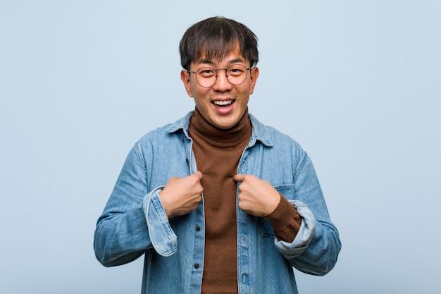 若い中国人男性は驚き、成功と繁栄を感じる
