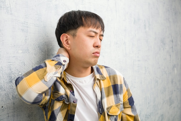 首の痛みに苦しんでいる若い中国人男性の顔のクローズアップ