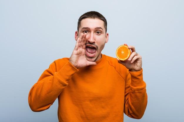 オレンジ色の叫びを保持している若い白人男は前に興奮しています。