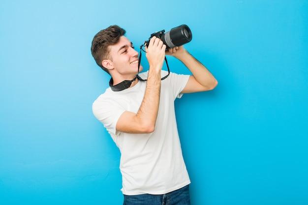 Подросток кавказских человек фотографировать с зеркальной камерой