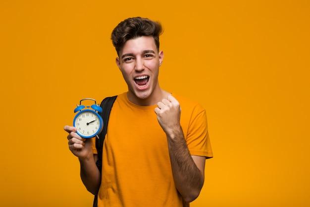 勝利または成功を祝う目覚まし時計を保持している若い学生男