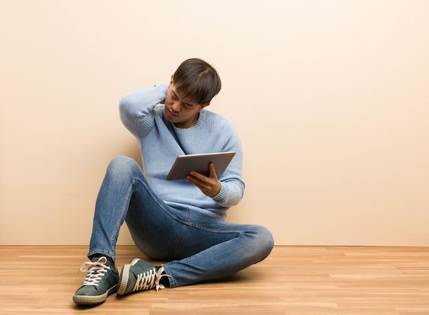 首の痛みに苦しんでいる彼のタブレットを使用して座っている若い中国人男性