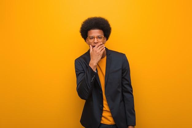 Молодой бизнес афроамериканец человек над оранжевой стеной усталый и очень сонный