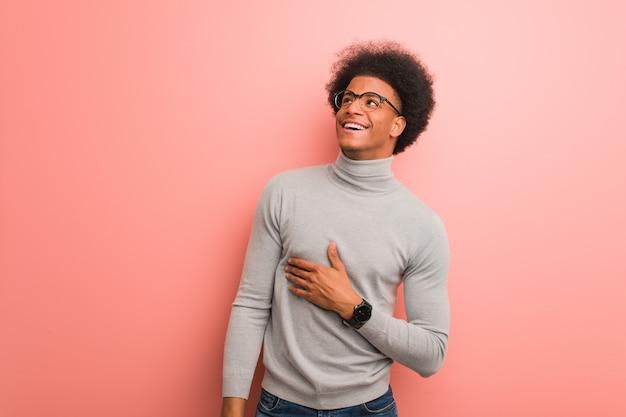 目標と目的の達成を夢見ているピンクの壁の上の若いアフリカ系アメリカ人