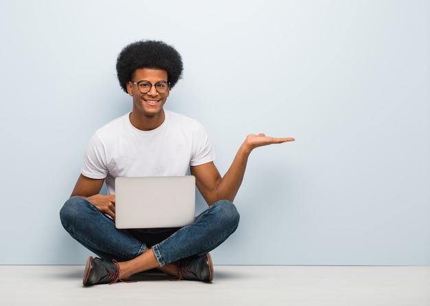 手で何かを保持しているラップトップで床に座っている若い黒人男性
