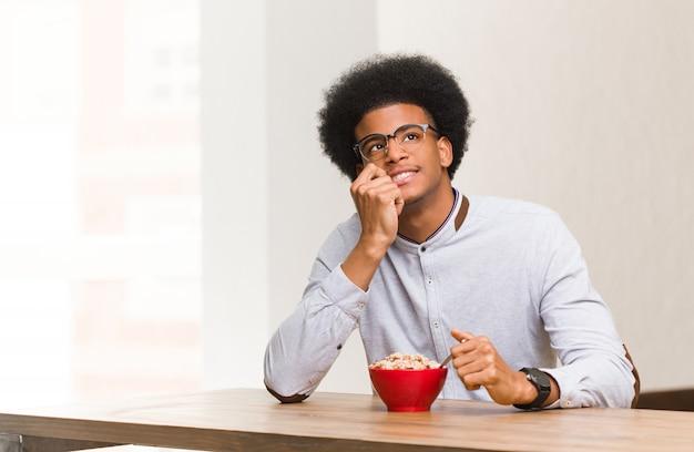朝食を持っている若い黒人男性がコピースペースを見て何かについてリラックスした思考