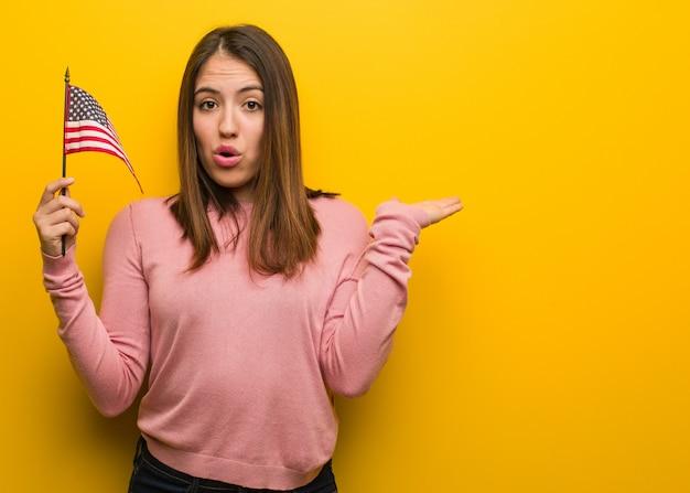 Молодая милая женщина держит флаг сша, что-то держит на ладони