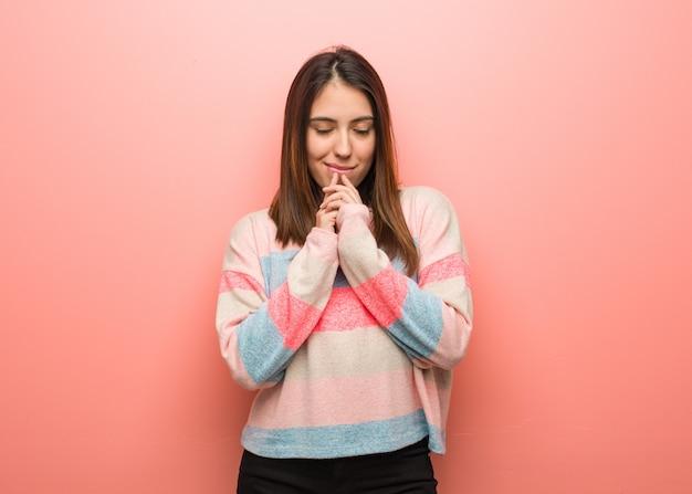 非常に幸せと自信を持って祈る若いかわいい女性