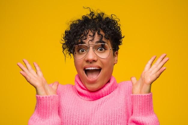 勝利または成功を祝うピンクのセーターを着ている若いアフリカ系アメリカ人女性、彼は驚き、ショックを受けています。