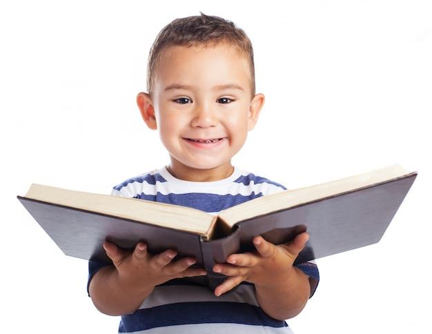 Маленький мальчик, улыбаясь с открытой книгой