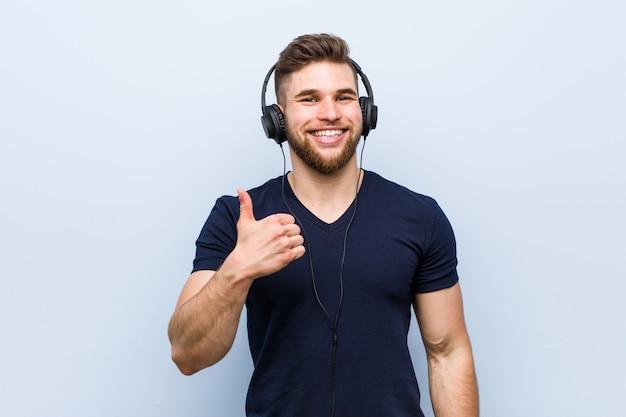 笑顔と親指を上げる音楽を聴く若い白人男