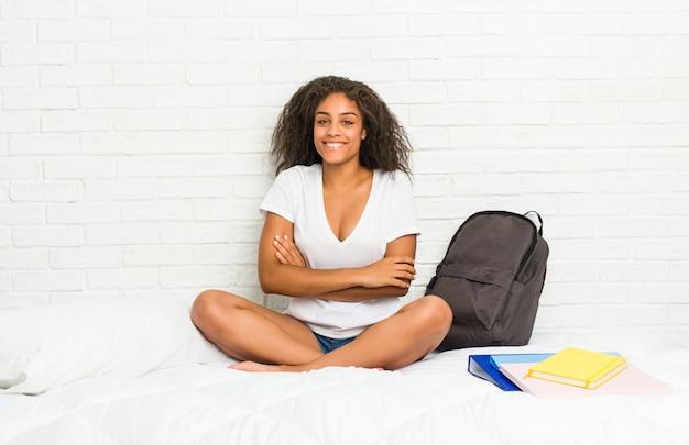 Молодой афро-американский студент женщина на кровати, который чувствует себя уверенно, скрещивая руки с решимостью.
