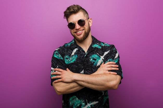 自信を持って、決意を持って腕を組んでいる休暇のルックを着ている若い男。