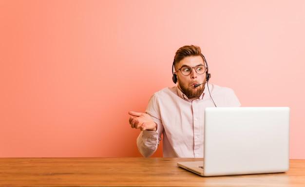 コールセンターで働く若い男は肩をすくめ、目を開けて混乱しています。