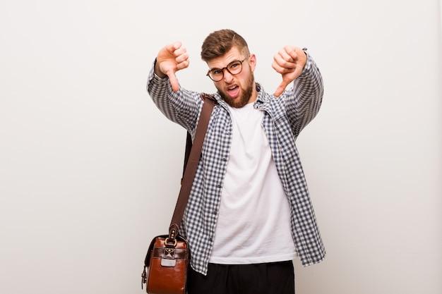 Молодой современный деловой человек, показывая большой палец вниз и выражая нелюбовь.
