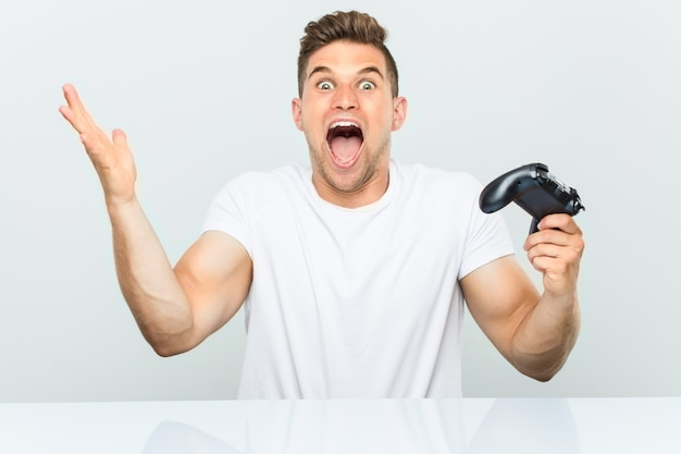 勝利または成功を祝うゲームコントローラーを保持している若い男