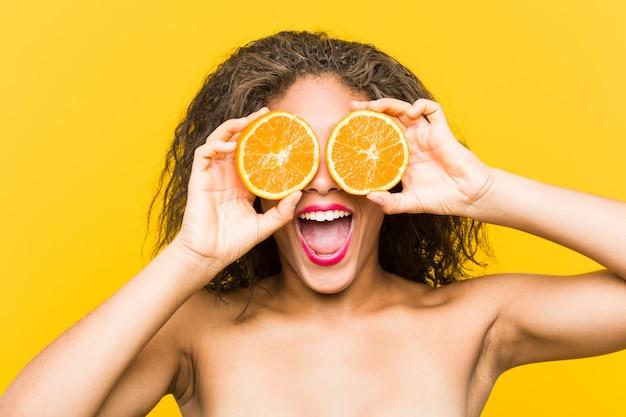 Крупным планом молодых афро-американских красивых и макияж женщина, держащая грейпфрут