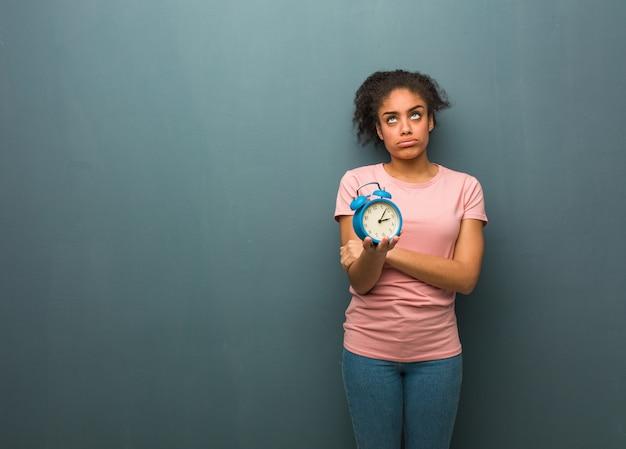若い黒人女性は疲れていて退屈しています。彼女は目覚まし時計を持っています。
