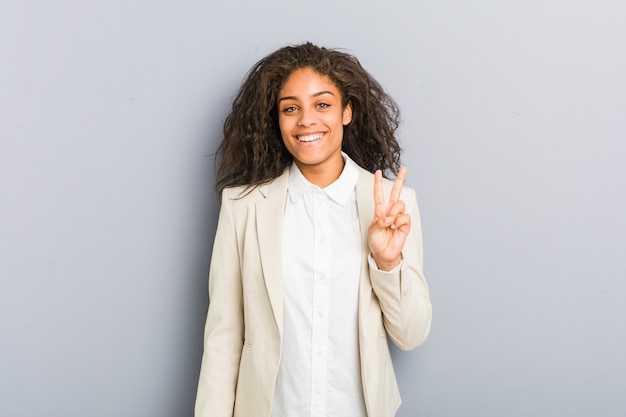 勝利のサインを示し、広く笑顔若いアフリカ系アメリカ人ビジネスの女性。